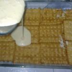 اضافة طبقة القشطة فوق طبقة البسكويت
