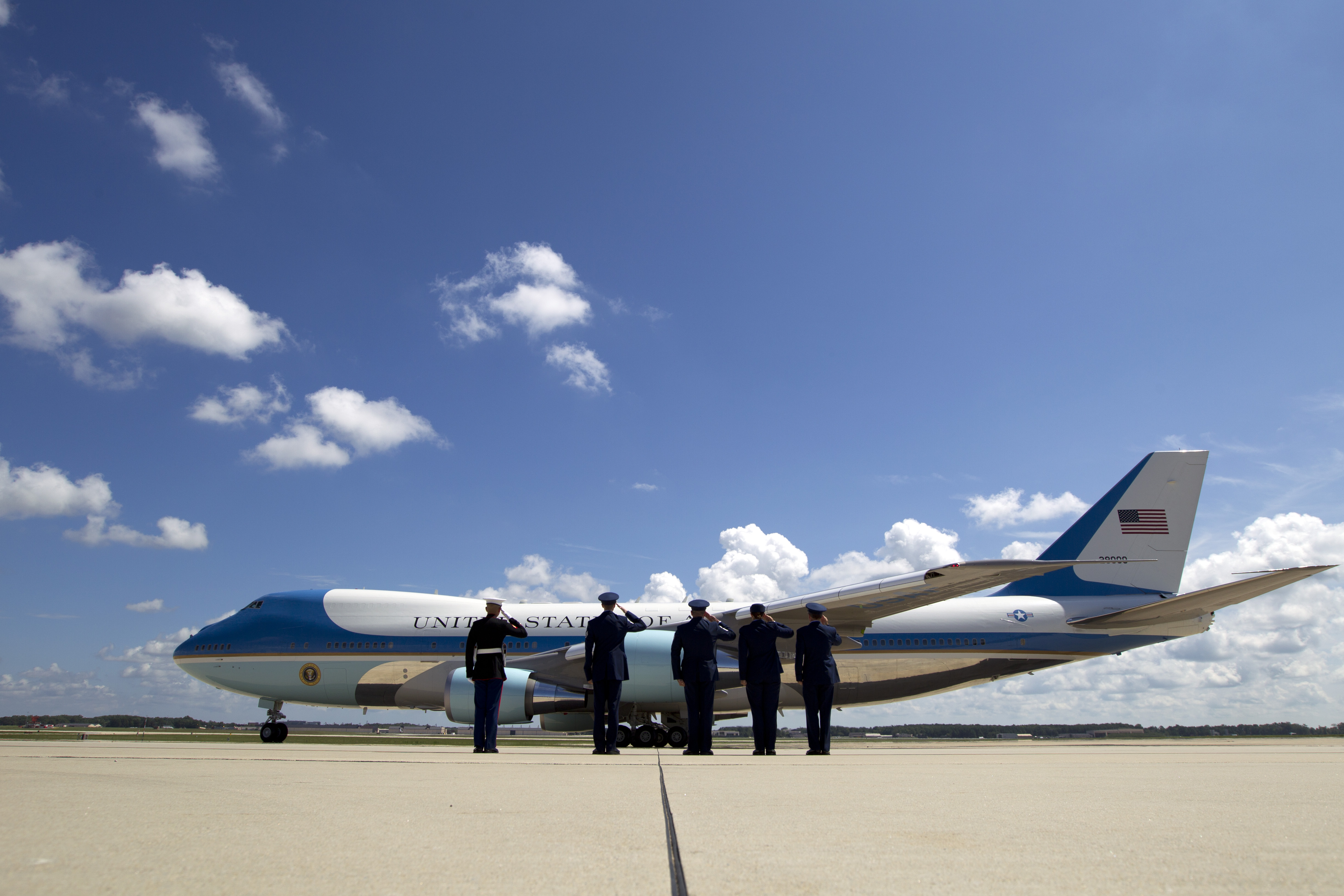 Military personnel salute Air Force One