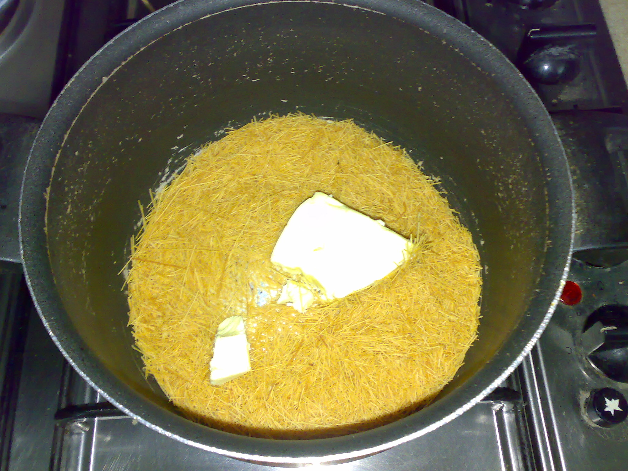 تحمير الشعيريه على النار مع الزبدة ليصبح لونها ذهبي