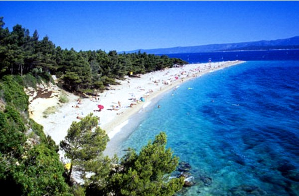 Windsurfers and swimmers are seen on a beach known as the Zlatni rat